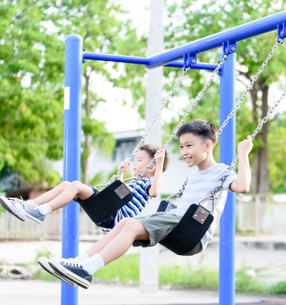 two kids enjoying the swings at the playground